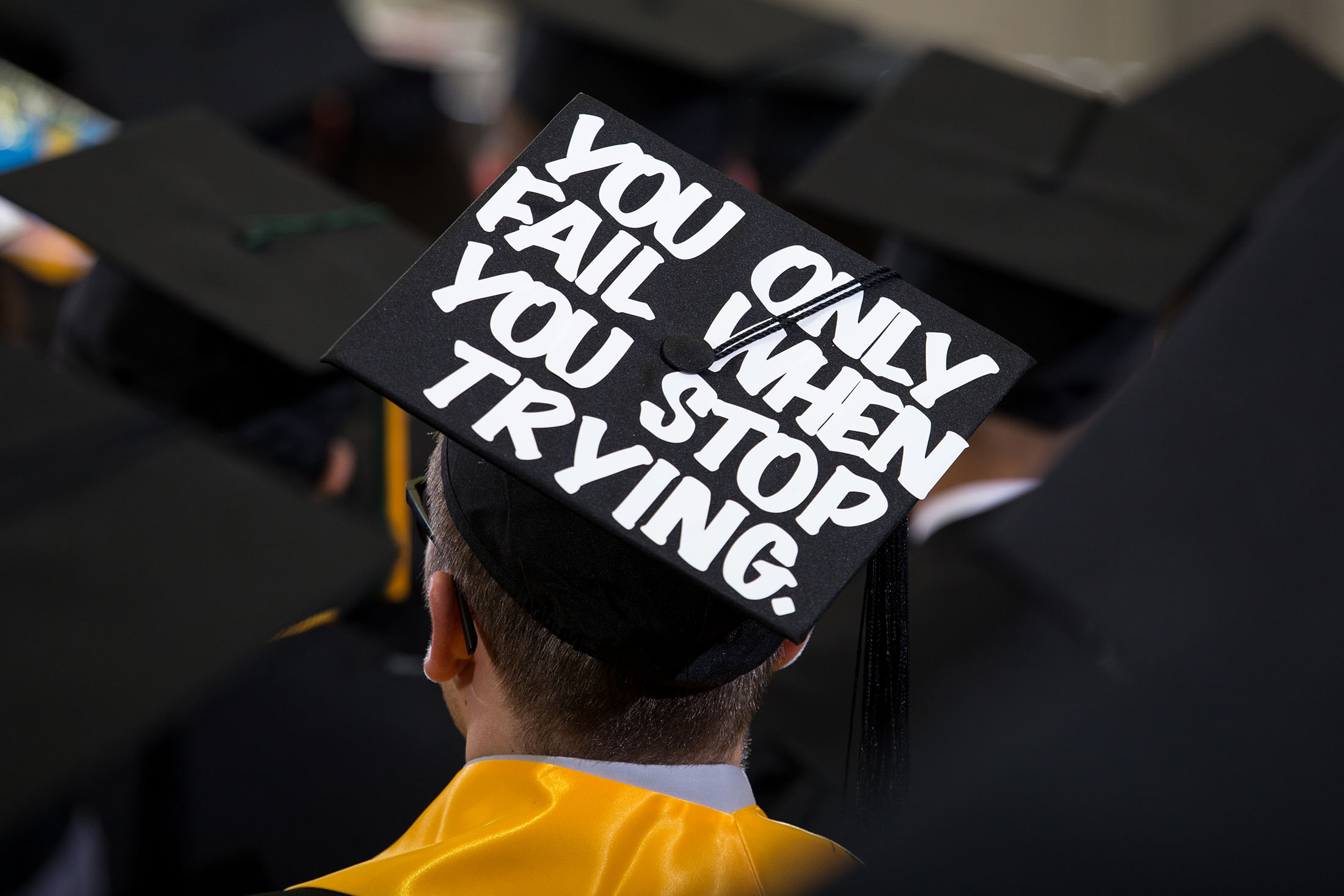 a student at graduation with a cap decorated to say you only fail if you stop trying
