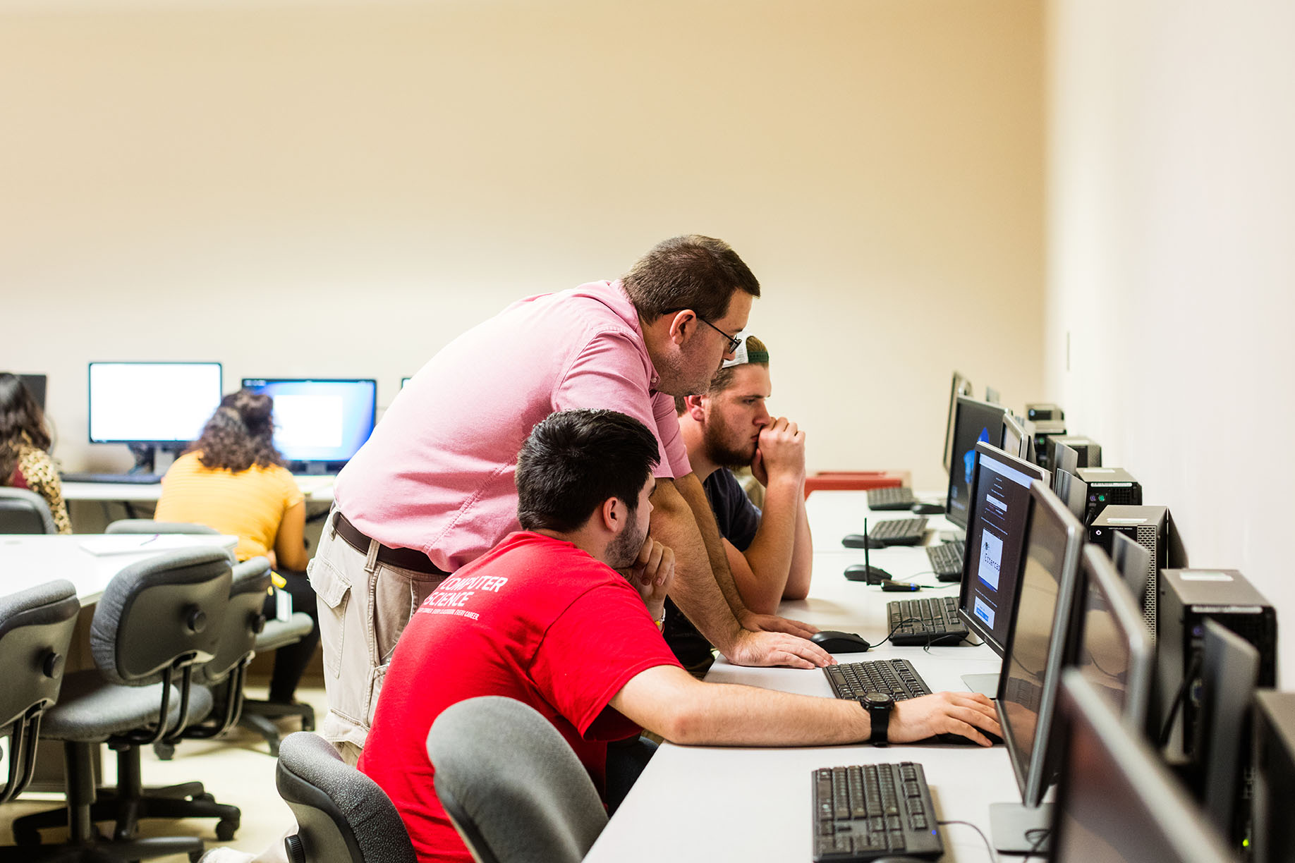 cybersecurity students work with a faculty to learn programming fundamentals