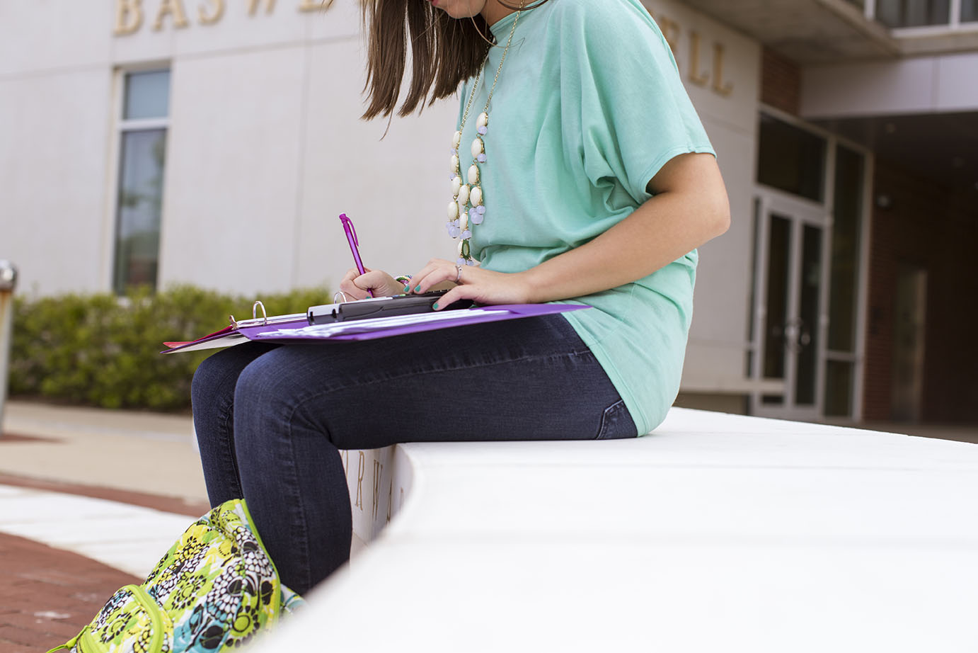 a student sits outside taking notes in her notebook