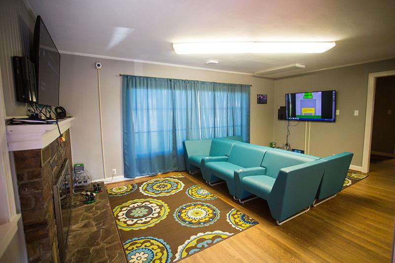 A room featuring sofas, televisions, cameras and gaming systems.
