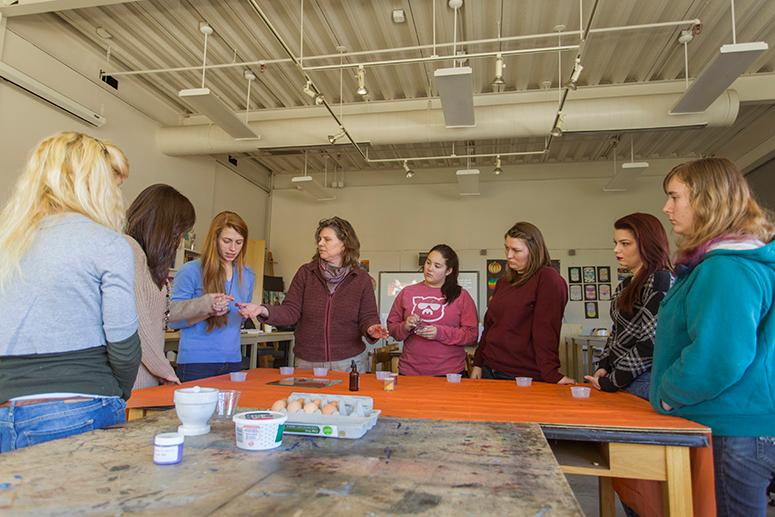 A professor works with students in the art education studio
