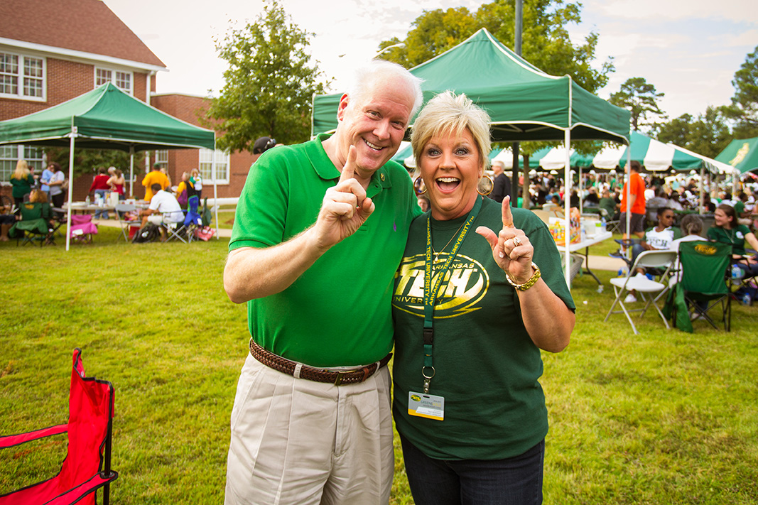 Two people dressed in Arkansas Tech garb pose at an outdoor event