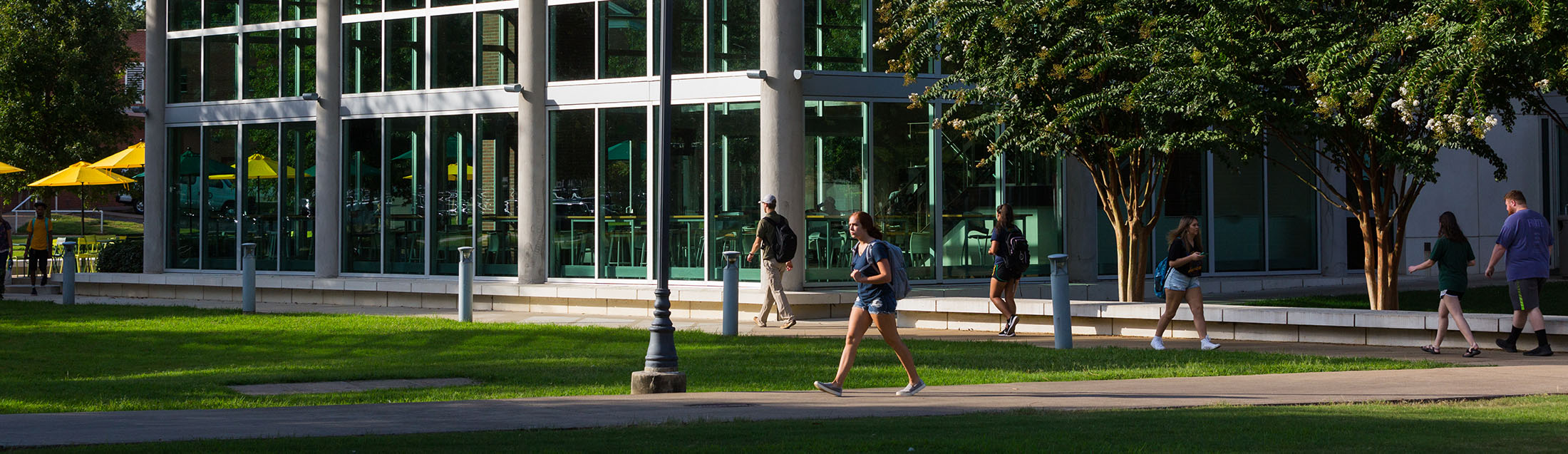 a student walking on campus in front of baswell techionery