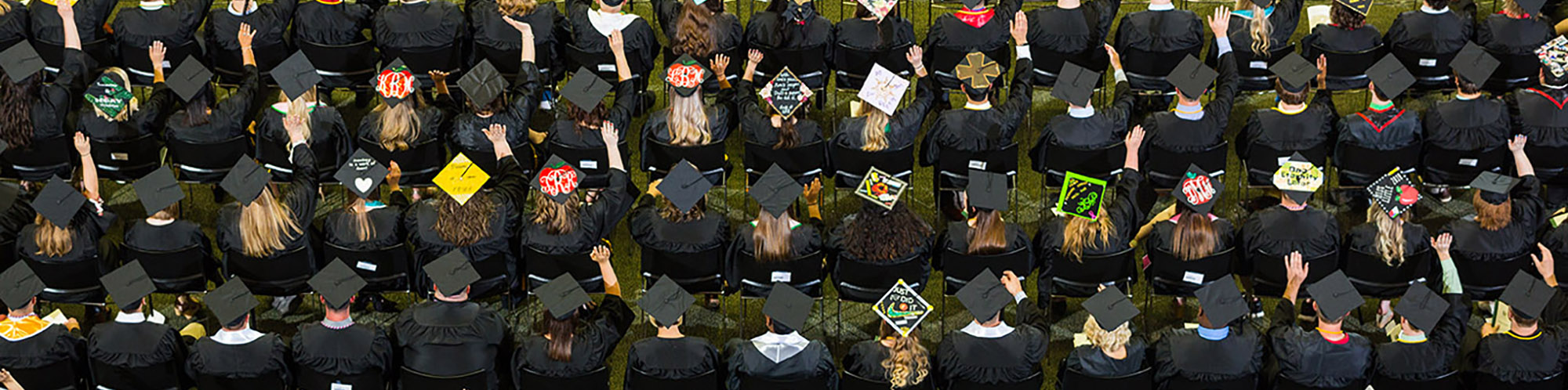 students showing off their decorated graduation caps at spring commencement