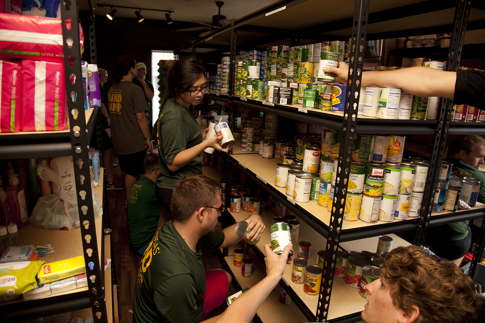 Green and Gold Cupboard volunteers stack cans.