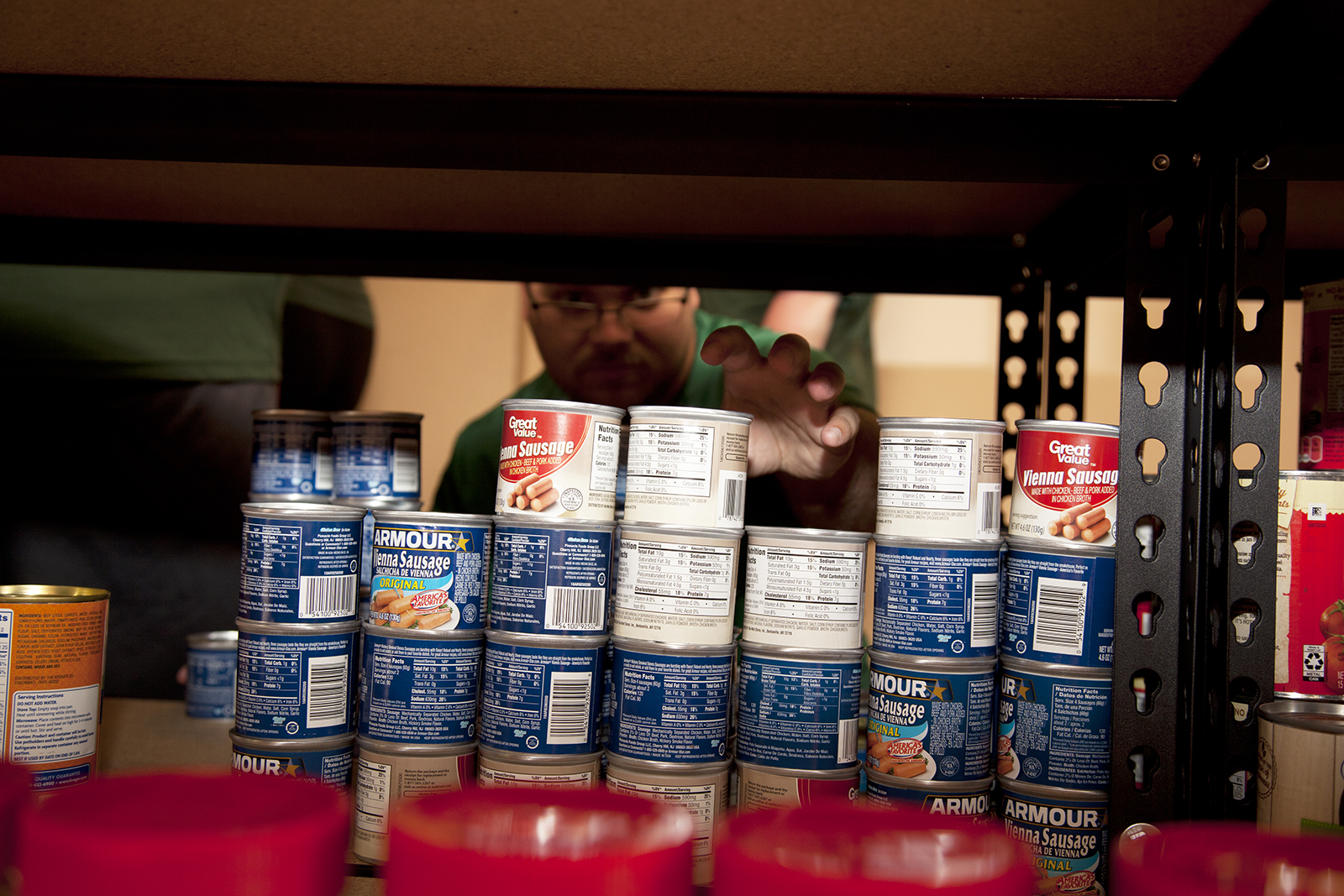 Green and Gold Cupboard Volunteer grabs a can of food.