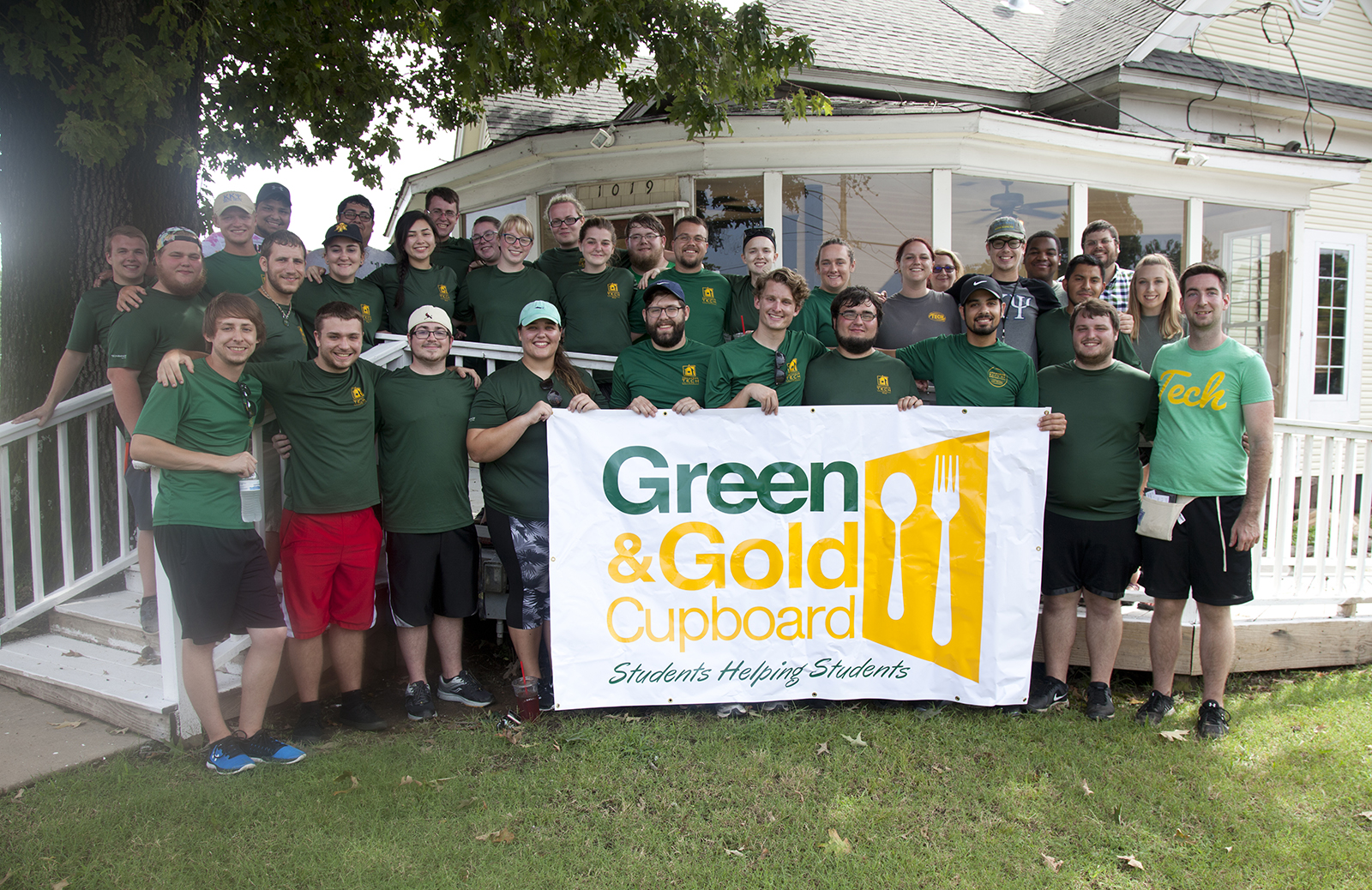 Volunteers stand outside the Green and Gold Cupboard.