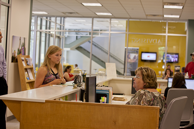 photo of a staff member helping a student in the academic advising center