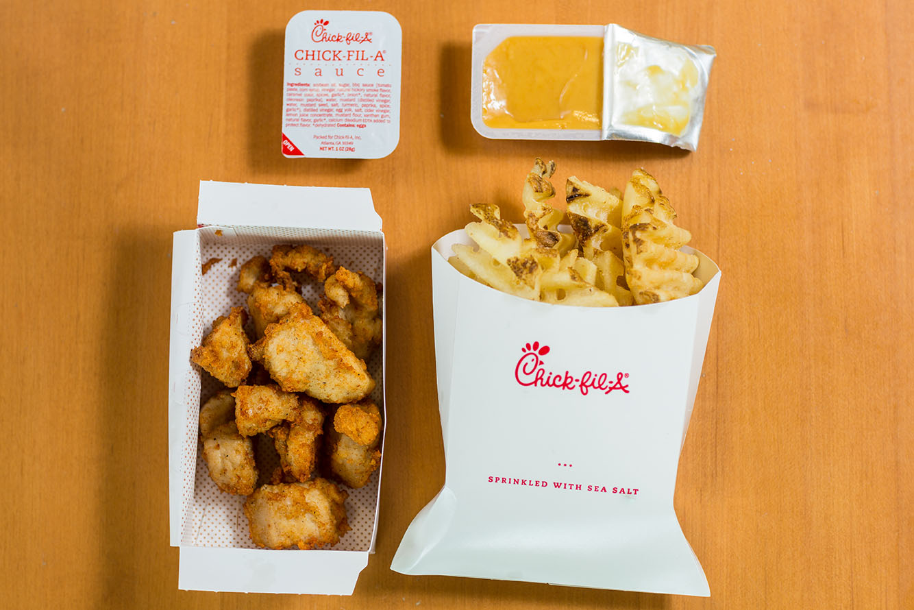 a photo of a Chick-Fil-A Chicken nuggets, french fries, and dipping sauces