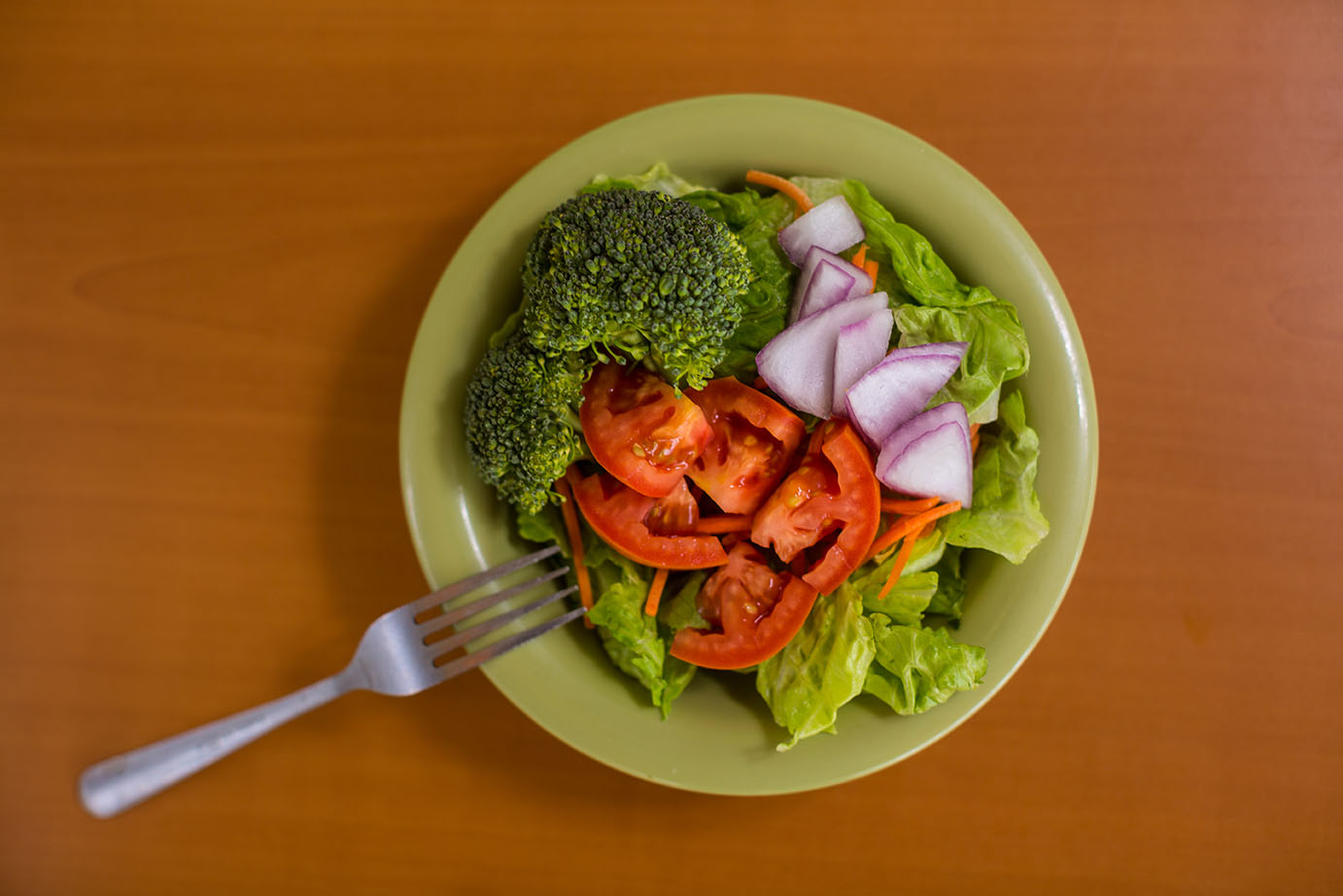 a photo of a mixed greens salad with carrots and red onion