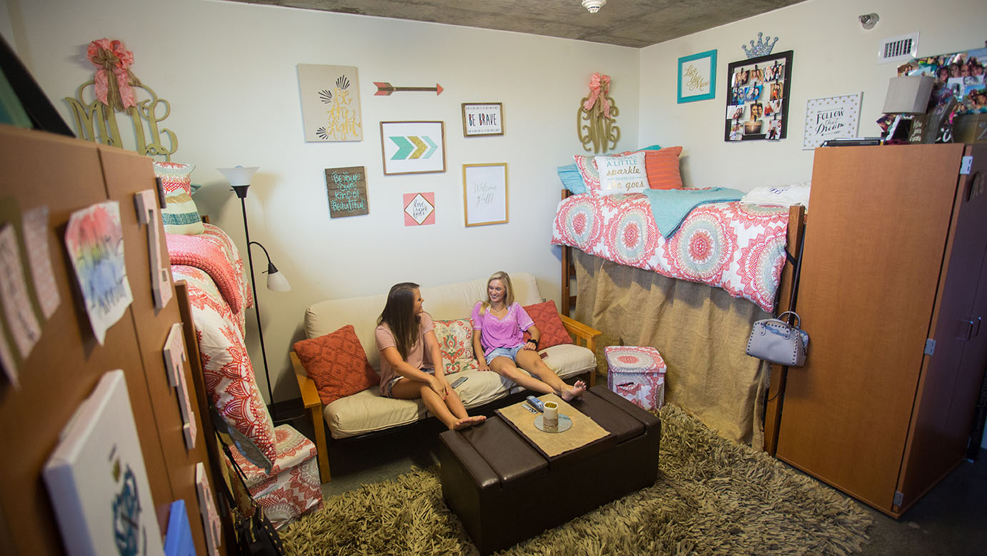 A photo of two female students sitting an a pink and tan decorated res hall room