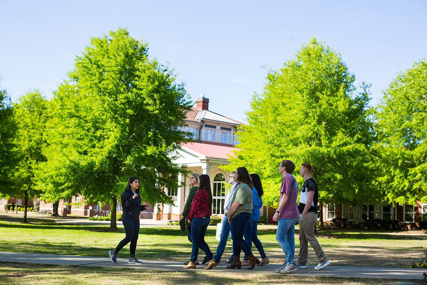 a student ambassador gives a group of new students a tour of campus