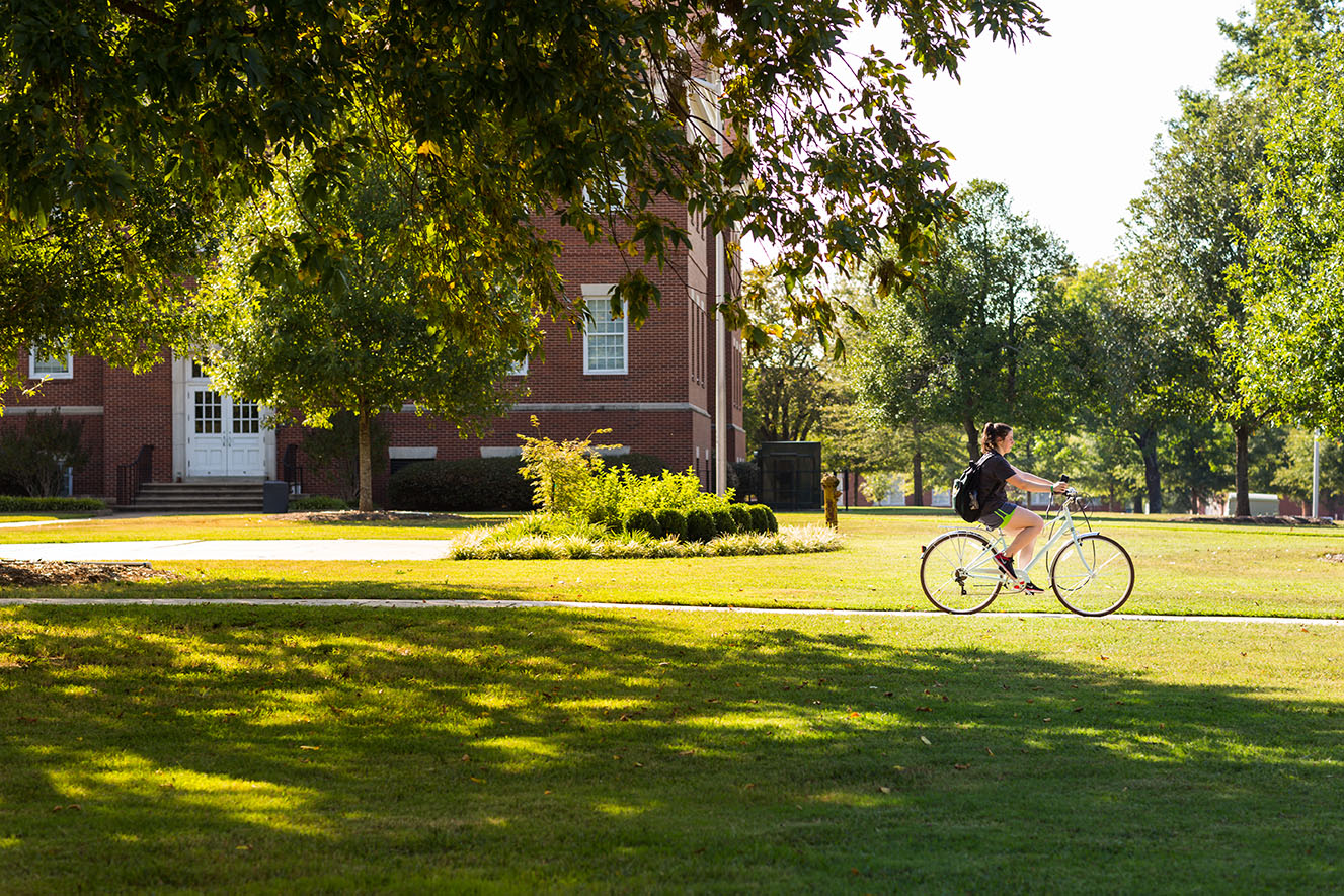 a photo of a student riding a bicycle on campus in the sunshine