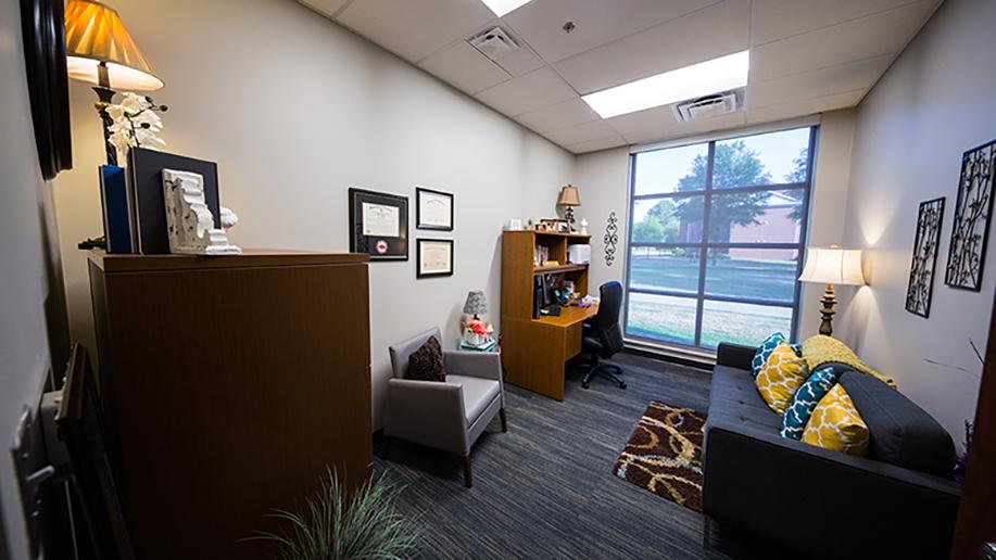 A counselor's office, with a couch, pillows, a chair, and a bookcase.