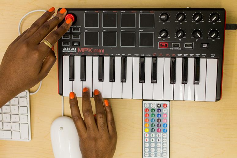 A close up photo of a woman's hands as she uses the sampler in the music lab