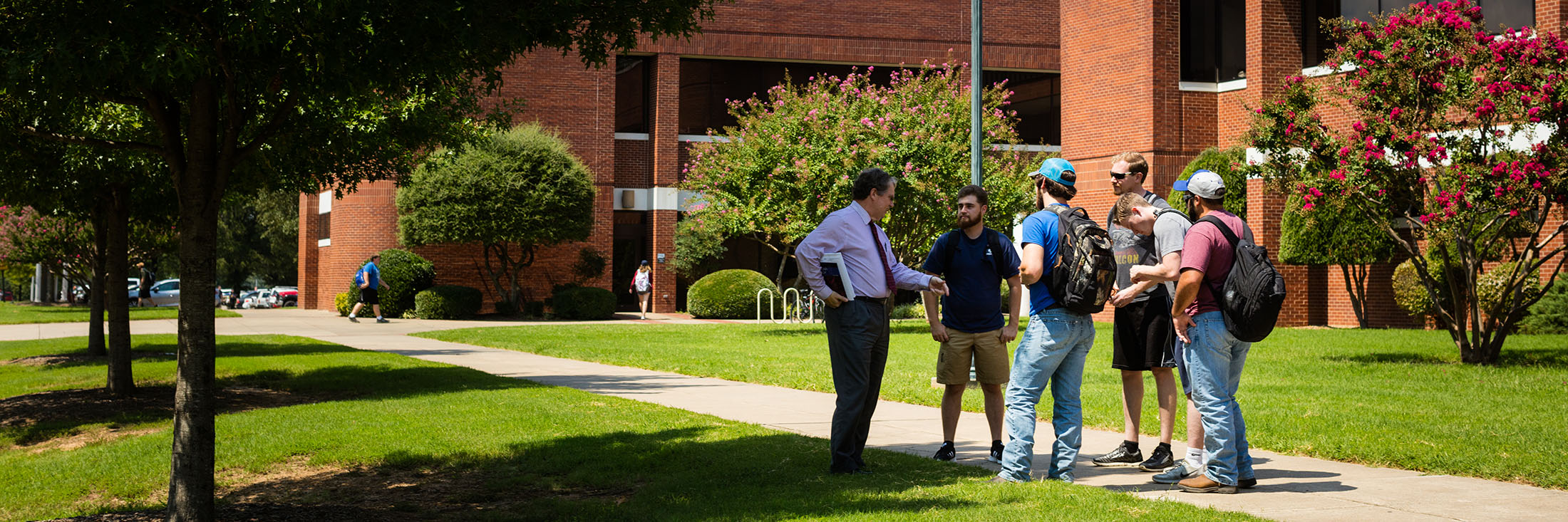 a group of students speak with a faculty member outside of corley hall