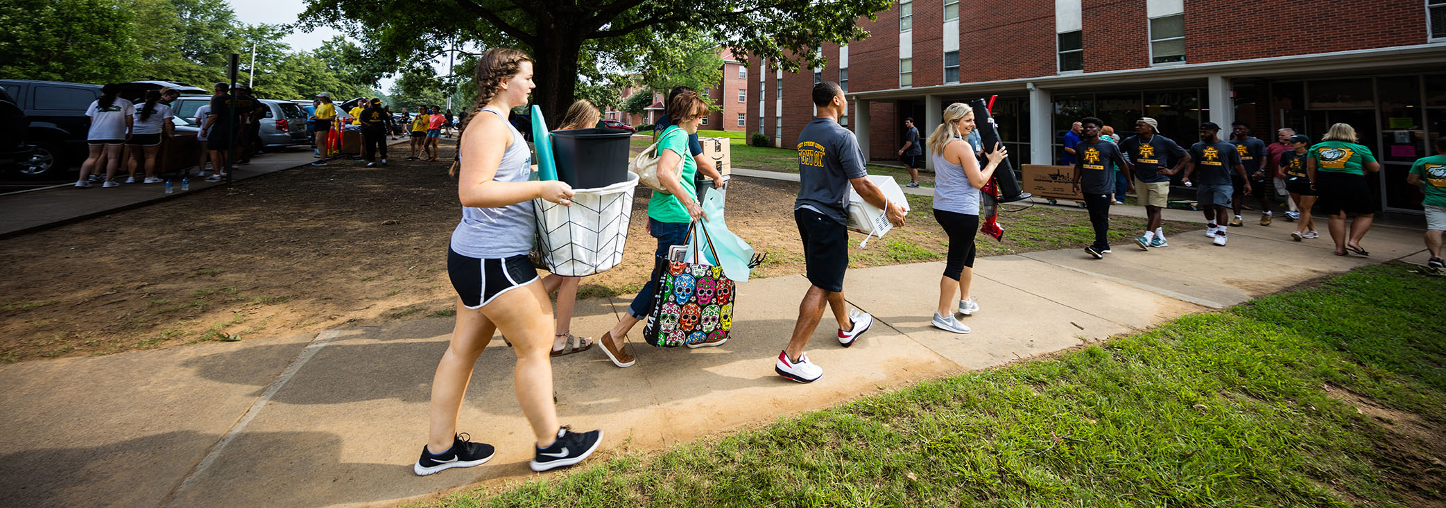 a group of new students move their belongings into a residence hall