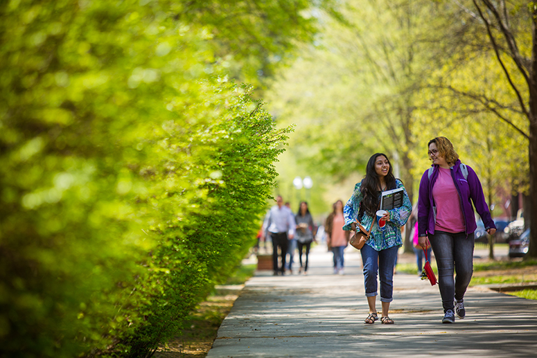photo of two student walking along a sidewalk on campus