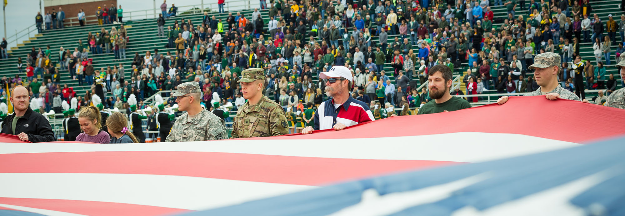 a group of veterans holding a large american flag at the 2017 ATU vs Harding football game